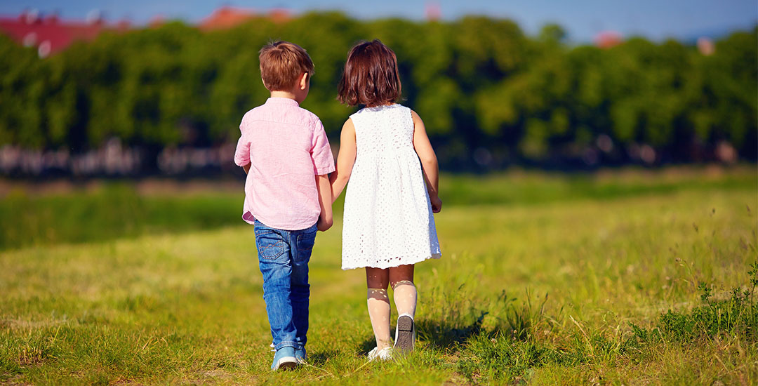 Two Cute Kids Walking Away On Summer Field